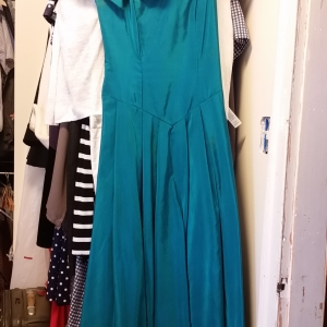 Peacock taffeta off-the-shoulder evening dress with huge bow and diamond buckle.